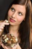 Chocolat - la jeune femme de verticale mangent la sucrerie Image libre de droits