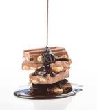 Chocolat liquide, tombant dans le groupe de morceaux de chocolat sur W images libres de droits