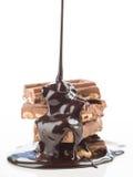 Chocolat liquide, tombant dans le groupe de morceaux de chocolat sur W images stock