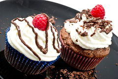 Chocolat muffins  with whipped cream and raspberries Royalty Free Stock Image