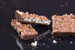 Chocolat noir avec du riz sur le fond de réflexion Images stock