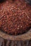 Chocolat râpé par amende dans la vieille cuillère en bois Photographie stock libre de droits