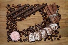 Chocolat-Stöcke und Meringe- und Zimtstange- und Kaffeebohnen und türkische Freude auf einem broun Holztisch lizenzfreies stockfoto