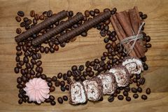 Chocolat sticks and meringue and cinnamon stick and coffee beans and turkish delight on a broun wooden table royalty free stock photo