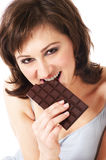 Chocolate. Pretty young woman eating chocolate Stock Images