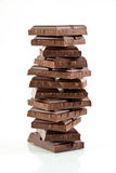 Chocolate. Tower of chocolate pieces isolated on white Stock Photography