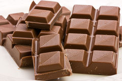 Chocolate. Delicious squares of milk chocolate piled on white plate Stock Images