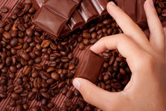 Chocolate. Children's arm takes a piece of chocolate on the background of coffee and chocolate Stock Image