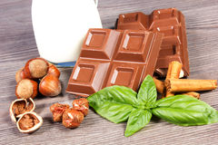 Chocolate. Choclate bars on the table with cinnamon and hazelnuts Royalty Free Stock Photography
