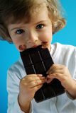 Chocolate. Beautiful four years old craving dark chocolate stock photo