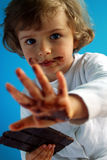 Chocolate. Little girl with dark chocolate on blue background stock photography