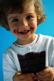 Chocolate. Little girl with dark chocolate on blue background Royalty Free Stock Images