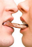 Chocolate. Young couple with chocolate in them mouth Royalty Free Stock Photography