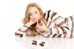 Chocolate Addict. A chocolate addict enjoying a selection of chcolate truffles Stock Photography