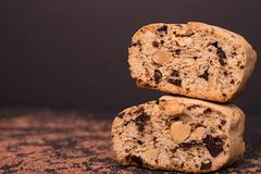 Two slice of italian biscotti. Food background. Chocolate almond biscotti, cantucсini. Slice of chocolate biscotti on a black background, detail, macro, close royalty free stock image