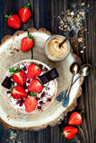 Chocolate almond butter maca smoothie bowl topped with sliced strawberries, chopped chocolate and pomegranate seeds Royalty Free Stock Photos