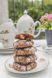 Chocolate and almond cookies. On plate with tea set and flowers in the background Stock Image