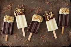 Chocolate and almond dipped white and dark popsicles on rustic metal. Chocolate and almond dipped white and dark popsicles, on rustic metallic background Stock Photo