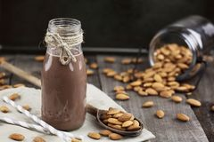 Chocolate Almond Milk. In a glass bottle with whole almonds spilled over a rustic wooden table Stock Image