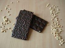 Chocolate amargo com pinhões Porca de cedro perto da barra de chocolate Imagens de Stock Royalty Free