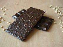 Chocolate amargo com pinhões Porca de cedro perto da barra de chocolate Fotografia de Stock Royalty Free