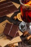 Chocolate amargo tajado con el vidrio de vino y de especias reflexionados sobre Imagenes de archivo