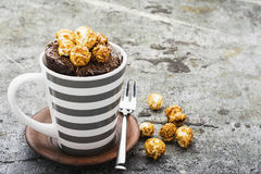 Chocolate aromatic mug cake with caramel appetizing popcorn for autumn cozy warm tea drinking on a gray stone background. In a stylish gray striped mug royalty free stock photography