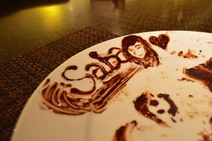 Chocolate art on a plate - Saba Malaysia with a smiling girl's face and a heart royalty free stock photos