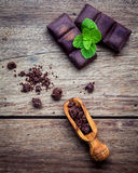 Chocolate background and dessert menu. Ingredients for bakery ch. Ocolate bar with mint ,chocolate powder in wooden spoon setup on dark shabby wooden background Royalty Free Stock Photos