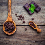 Chocolate background and dessert menu. Ingredients for bakery ch. Ocolate bar with mint ,chocolate powder in wooden spoon setup on dark shabby wooden background Royalty Free Stock Photography