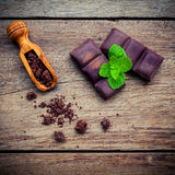 Chocolate background and dessert menu. Ingredients for bakery ch. Ocolate bar with mint ,chocolate powder in wooden spoon setup on dark shabby wooden background Royalty Free Stock Photo