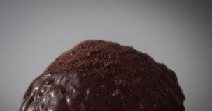 Chocolate ball covered by liquid syrop and cacao powder. Chocolate ball covered by liquid chocolate syrop and cocao powder walling on it stock video footage