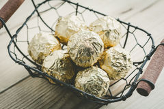 Chocolate ball with golden foil in a basket, vintage color tone.  Royalty Free Stock Photos
