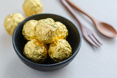 Chocolate ball with golden foil in a black cup.  Royalty Free Stock Photography