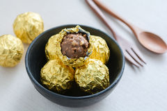 Chocolate ball with golden foil. In a black cup Royalty Free Stock Images