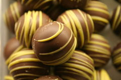 Chocolate balls. A pile of tasty chocolate truffles with yellow stripes Stock Photos