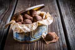 Chocolate balls in blue box. On old wooden table Royalty Free Stock Images