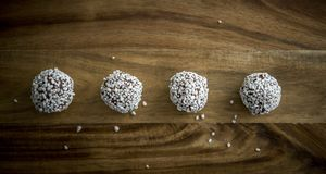 Chocolate balls on a brown chopping board. With bits of granulated sugar Stock Photography