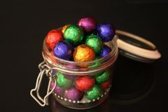 Chocolate balls in a candy jar Stock Images