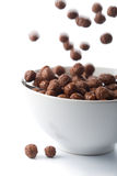 Chocolate balls falling into bowl isolated Stock Photography