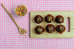 Chocolate balls with fancy topping on wooden plate Royalty Free Stock Image