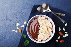 Chocolate banana almond coconut smoothie bowl on stone table top view. Healthy breakfast or dessert. Flat lay. stock images