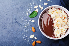 Chocolate banana almond coconut smoothie bowl on stone table top view. Healthy and diet breakfast or dessert. Flat lay. Royalty Free Stock Images