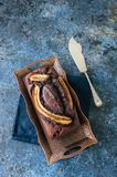 Chocolate banana date dread on a vintage tray on a blue stone ba. Ckground. Copy space Royalty Free Stock Image