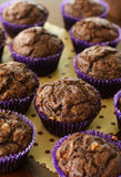 Chocolate banana muffin. A batch of chocolate banana muffins arranged randomly on a wooden surface Stock Photo