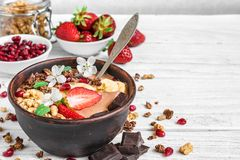 Chocolate banana protein smoothie bowl with granola, strawberry, pomegranate and chocolate bars topped with flowers stock photo