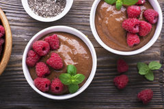 Chocolate Banana Smoothies served fresh juicy ripe raspberries with a sprig of mint in portioned bowls on  wooden Royalty Free Stock Photos