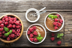 Chocolate Banana Smoothies served fresh juicy ripe raspberries with a sprig of mint in portioned bowls on  wooden Royalty Free Stock Photo