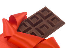 Chocolate bar. A sweet chocolate bar in a red silk ribbon envelopment. Special gift for Valentine's Royalty Free Stock Photography