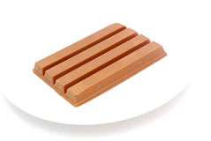 Chocolate bar. A big brown chocolate bar on a plate. Image isolated on white studio background Royalty Free Stock Photography